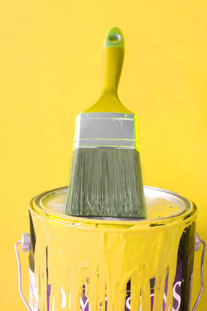 paintbrush on top of yellow  paint can for home decorating Stock Photo