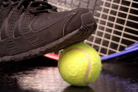 raquet: black sports sneaker on green tennis ball with raquet in the background