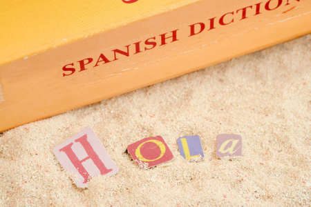 spanish hello hola on sandy tropical beach with spanish dictionary in the background