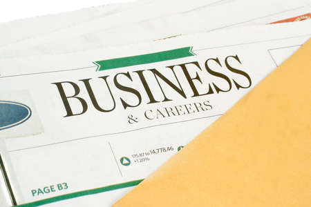 business section of the newspaper with yellow envelope Фото со стока