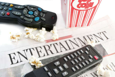 listings: entertainment section of the newspaper with television remote controls and popcorn