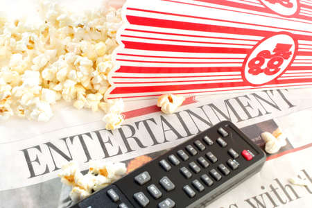 entertainment section of the newspaper with television remote controls and popcorn
