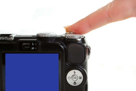 point and shoot: finger presses shutter release button on a point and shoot digital compact camera Stock Photo