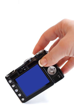 womans hand grabs for a point and shoot compact digital camera
