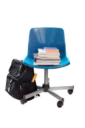 bookbag: school books and pencils on blue chair with wheels while bookbag lays to the side with ruler and pens sticking out Stock Photo