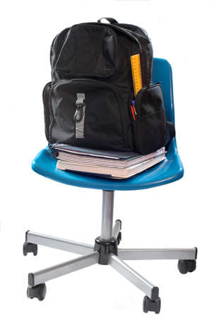 bookbag: school books and bookbag with ruler and pencils sticking out on a blue chair with wheels