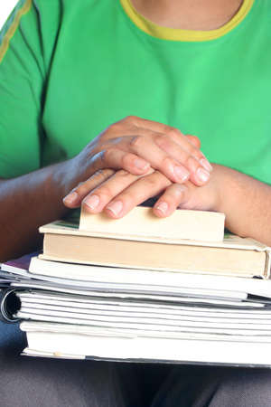 African American college male student with books on his lap and crossed hands Stock Photo