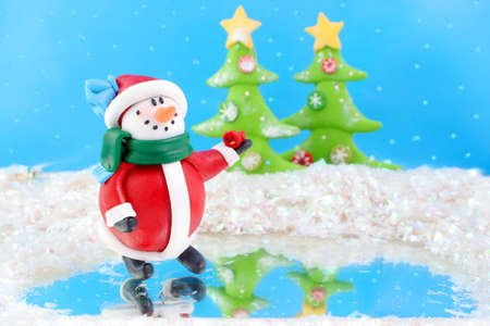 fantasy wonderland scene with  snowman skating on ice and christmas trees in the background photo