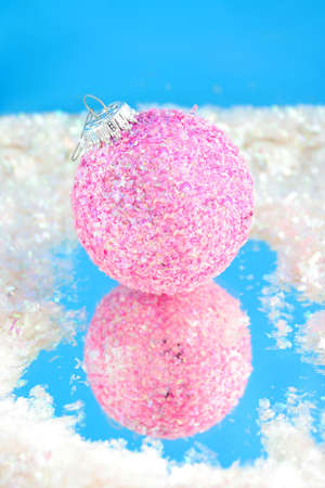 pink sparkly christmas ball with reflection on blue surrounded by fake snow