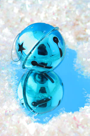 blue  christmas bell with reflection on blue surrounded by fake snow Stock Photo