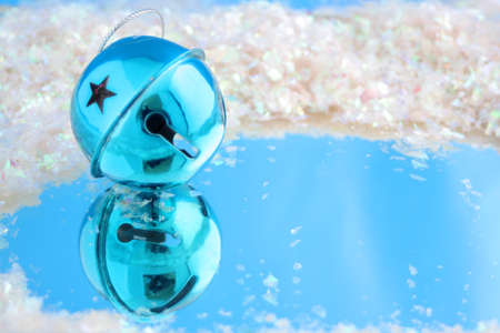 blue christmas bell with reflection on blue surrounded by fake snow