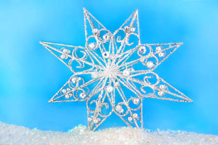 sparkly christmas star on blue background and glitter snow