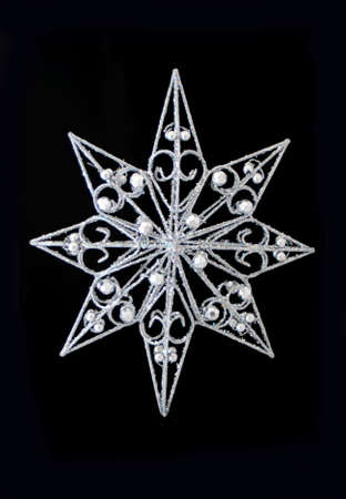 a sparkly christmas star ornament on black background