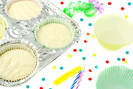 stiring: cake flour mix in baking pan with tinsel ribbons, candles, confetti, and extra cupcake paper cups on the side Stock Photo