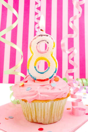 eighth: birthday cupcake with pink frosting and and decorative background celebrating childs eighth anniversary