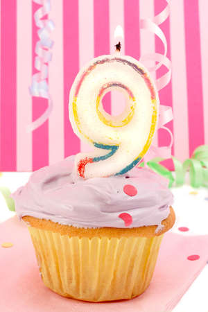 birthday cupcake with pink frosting and and decorative background celebrating child's ninth anniversary Stock Photo - 3460546