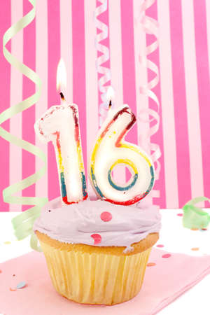 cupcake with purple frosting and and decorative pink background celebrating teenager's sixteenth birthday Stock Photo - 3469649