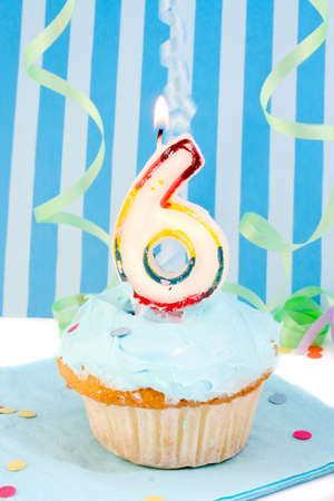 boys sixth birthday cupcake with blue frosting and  decorative background  photo