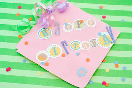 Happy birthday cut out letters on pink napkin with ribbons and confetti Stock Photo - 3487323