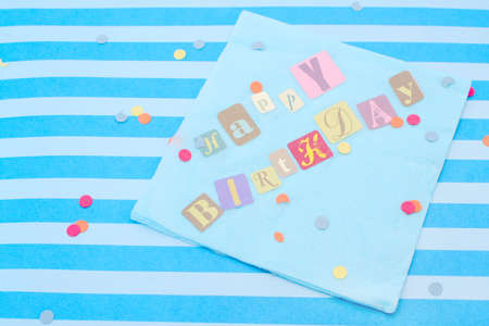 Happy birthday cut out letters on blue napkin with confetti Stock Photo - 3487321