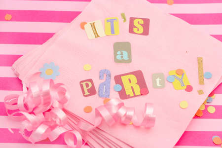 its: cut out letters spelling its a party on pink napkins with curled ribbons and confetti, great for invitation cards