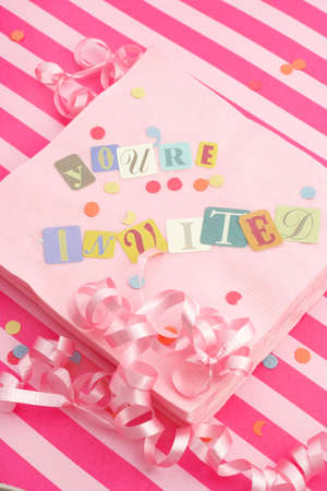 invited: cut out letters spelling youre invited on pink napkins with curled ribbons and confetti, great for invitation cards