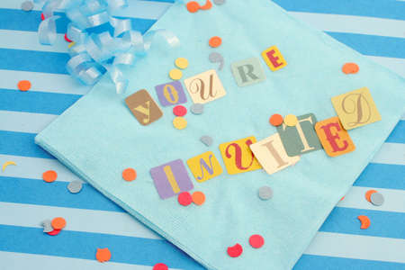 invited: cut out letters spelling youre invited on baby blue napkins with curled ribbons and confetti, great for invitation cards