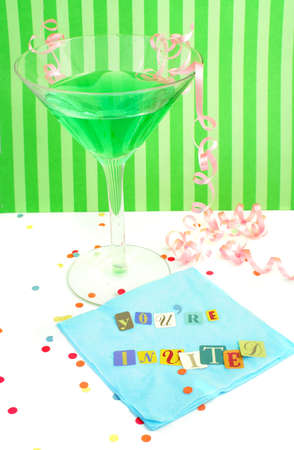 invited: Youre invited spelled out with cut out letters on blue napkin with blue martini with confetti and curled ribbons great for party invitations Stock Photo