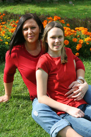 beautiful barefoot mother and daughter sitting on the grass with flowers in the background