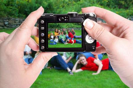 女性の手の公園で家族のグループのスナップショット写真を撮るカメラを保持します。