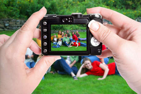 womans hands hold camera taking a snapshot picture of family group in a park Stock Photo