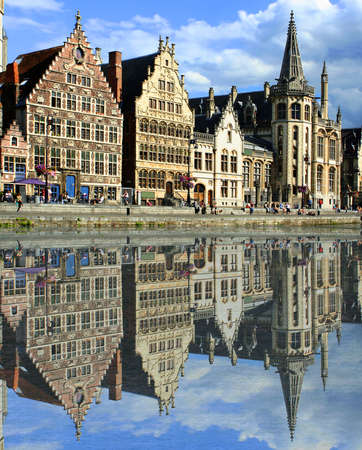 gabled: gabled houses along a canal  in Gent,  Belgium with reflection on the water