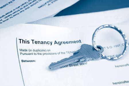 tenant: some paperwork concerning tenancy agreement with key in blue tone
