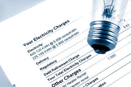 cuenta: bombilla en la factura de la luz y potencia indicando los gastos mensuales en tono azul Foto de archivo