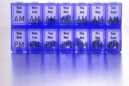 cures: different kinds of pills in slots of  daily reminder cannister Stock Photo