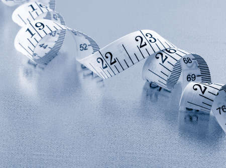 centimetres: curled up measuring tape on silver background