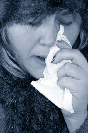 drippy: under the weather or feeling blue, sick woman with a flu holding tissue Stock Photo