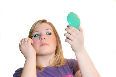 18 year old: pretty 18 year old teenager applies eye pencil makeup while holding compact mirror