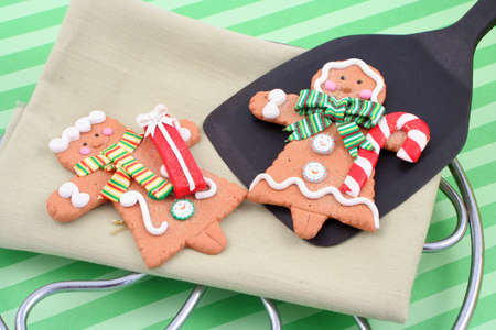 set of man and woman christmas gingerbread cookies, one is on a spatula fresh out of the oven photo