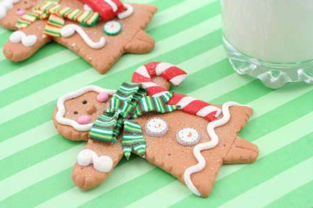 set of man and woman christmas gingerbread cookies on a napkin, with tall glass of cold milk photo