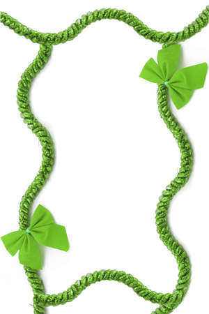 green background: green christmas tinsel and bow frame or border on a white background