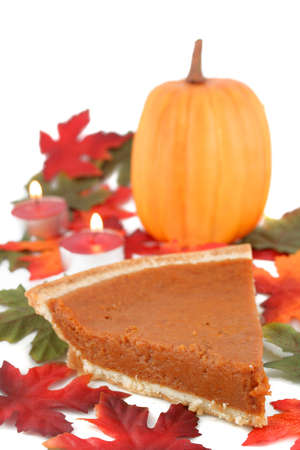 one piece of pumpkin pie on white plate surrounded by fall leaves,tea lights, and pumpkin in the  photo