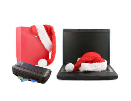 mobile laptop computer with santa christmas hat draped on the keyboard and red giftbag and wallet on the side