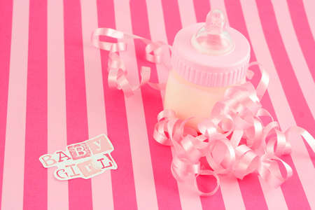 a pink  bottle with milk and celebratory ribbon suitable for new