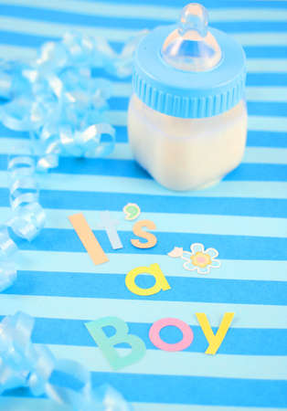 a blue baby bottle with milk and celebratory its a boy text and  ribbon suitable for new baby