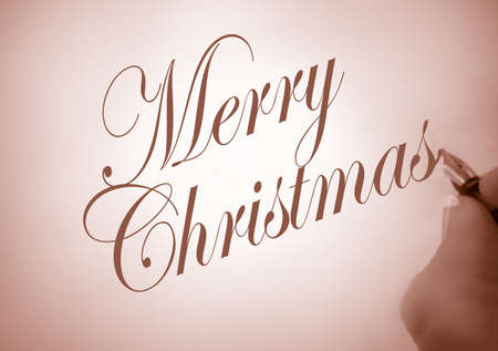 greeting christmas: person writing merry christmas in calligraphy in sepia