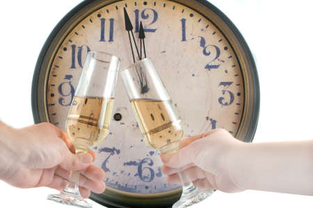 man and woman's hands make a toast with champagne glasses  with new years countdown vintage clock in the background Banque d'images
