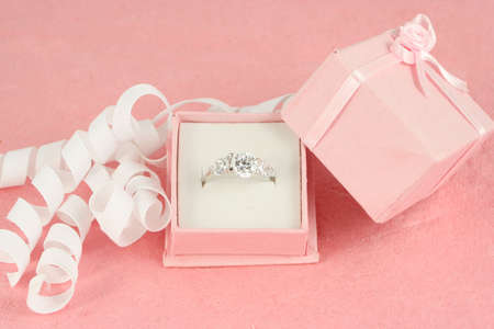 pink gift jewelry box holds a diamond engagement ring with ribbon