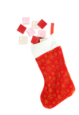 stuffed festive christmas stocking hanging with small gift boxed hanging out isolated on a white background