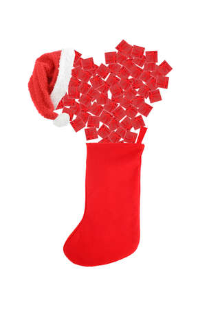 stuffed festive christmas stocking overflowing with small red  gift boxes isolated on a white background Stock Photo